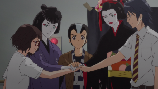 A group of high schoolers stand in a circle, their hands atop one another's in the center. From left to right: A girl in a school uniform and glasses; a girl in masculine traditional Japanese kabuki clothes; a boy wearing a wig and traditional clothes; a tall person wearing a kimono and traditional feminine kabuki makeup; and another boy wearing a school uniform