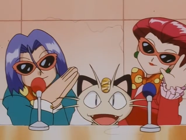 Team Rocket sitting behind microphones. Jessie and James are wearing brightly colored suits, bow ties, and sunglasses. Meowth sits between them. All three are smiling cheerfully.