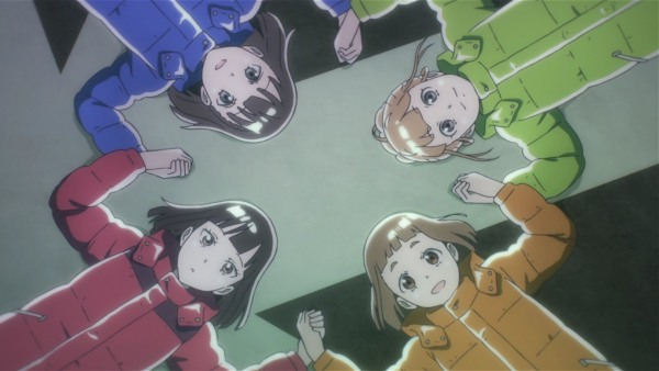 Four teen girls wearing multicolored parks lie on their backs, holding hands and looking up at the sky