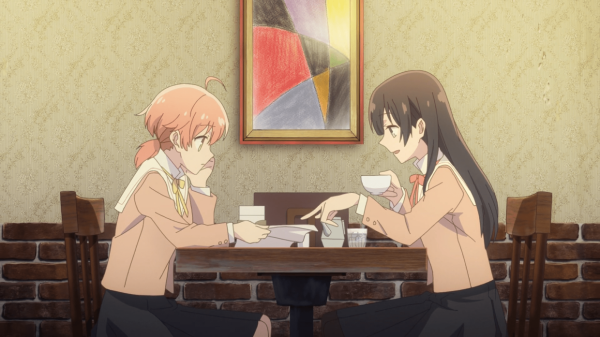 Two teen girls sit at a table in a coffee shop, looking at a set of papers in one girl's hand.