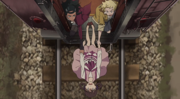 A girl hangs from the back of a train. Two people, a Spanish woman and a blonde boy, grab hold of her hands to keep her from falling.